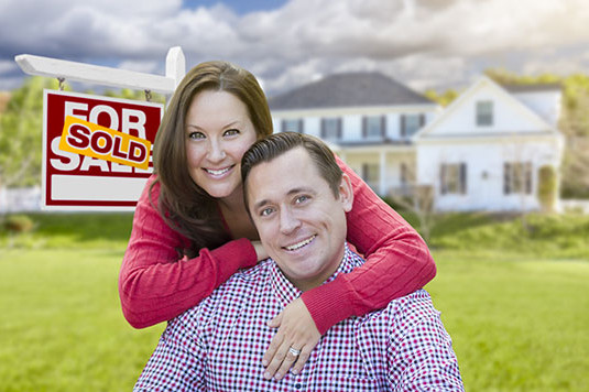 Happy Couple In Front of Sold For Sale Real Estate Sign and Beautiful House.
